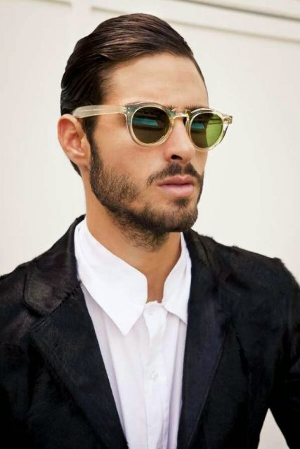 Modelo usa camisa branca, blazer preto e óculos masculino redondo.