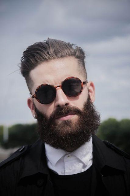Modelo usa óculos com armação estampada, camisa branca e blazer preto.