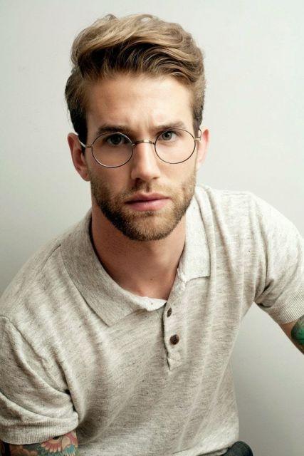 Modelo usa camiseta polo, óculos de grau armação fina.