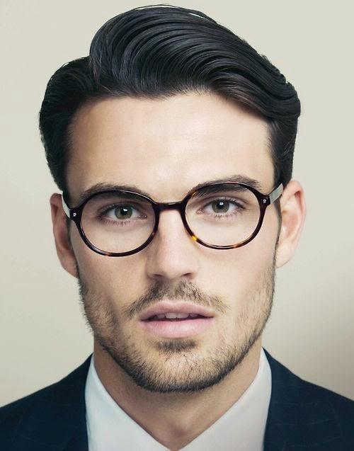Modelo usa terno e óculos de grau com armação preta.