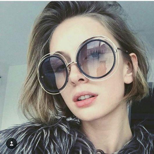 8988e79ad Modelo usa casaco cinza, óculos de sol redondo grande com cabelos soltos.