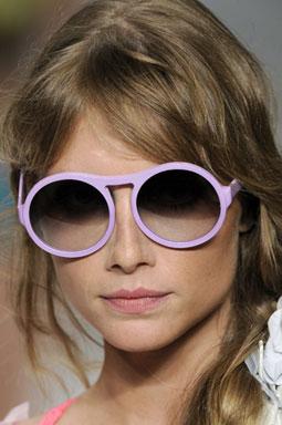 Modelo usa cabelo com trança lateral e óculos escuros redondo com armação lilás.