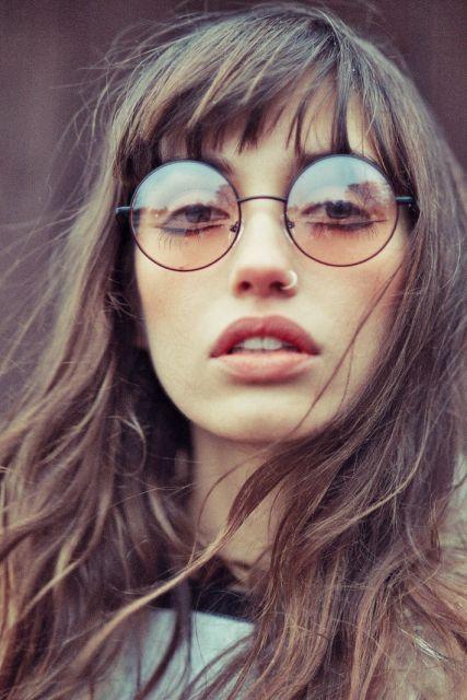 Modelo usa cabelo solto, blusa cinza com gola preta e óculos de sol redondo lentes de tamanho médio em tonalidades nude.