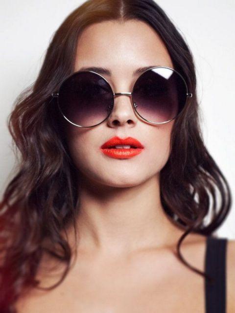 fd1b2d753 Modelo veste blusa de alça preta, cabelo soltos ondulados e óculos de sol  redondo grande