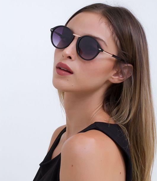 Modelo usa blusa regata preta com óculos de lentes escuras.