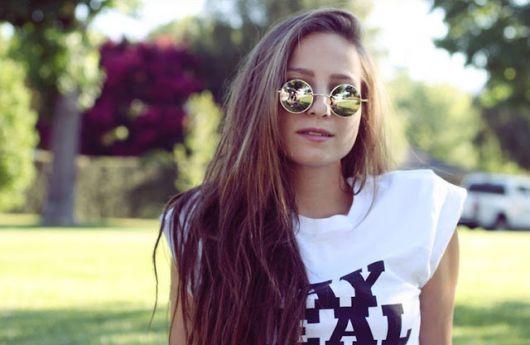 Modelo usa camiseta branca estampada e óculos de sol lente pequena redonda.