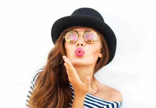 Modelo usa blus branca com listras azuis, chapéu feminino preto e óculo redondo de lentes pequenas espelhadas.