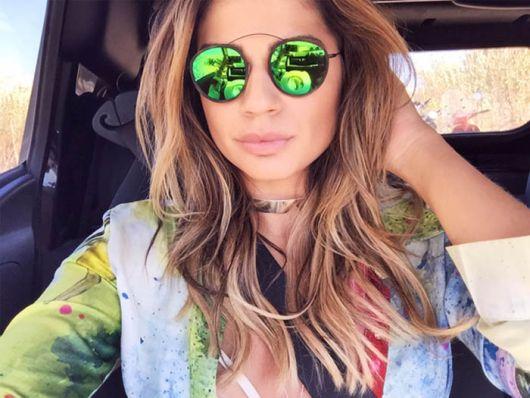 Modelo usa blusa verde, colete jeans e óculos de sol com lentes verdes.