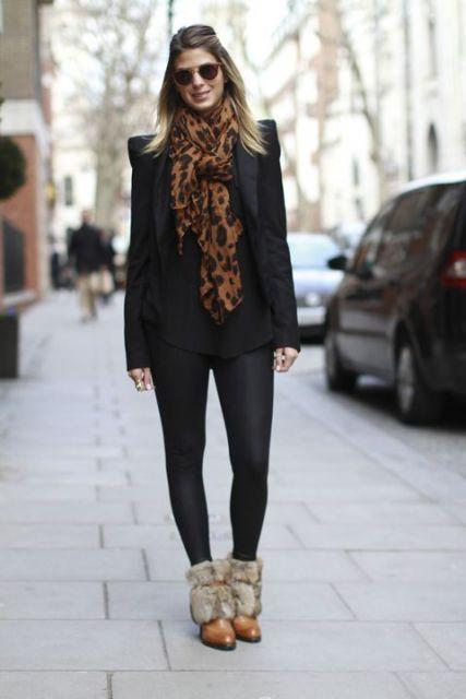 Modelo usa calça preta, botinha rasteira com pelucia, blazer preto e cachecol estampa de onça cor terra.