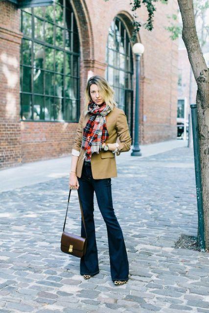 Modelo usa calça flare jeans, jaquetinha cor terra, cachecol xadrez e bolsa de ombro marrom tamanho médio.