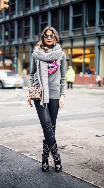 Modelo usa cachecol cinza, moletom na mesma cor, calça preta, botinha e bolsa transversal.