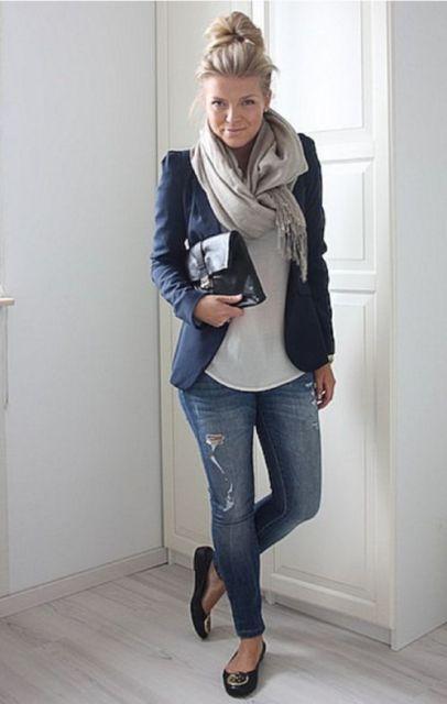 Modelo usa cachecol cinza, calça jeans, blusa branca, blazer azul e sapatilha.
