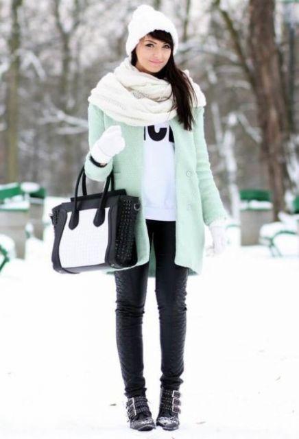 Modelo usa casaco azul clarinho, calça preta, botas, bolsa preta, cachecol e gorro branco.