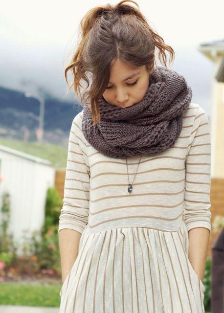 Modelo usa cachecol marrom de tricô, vestido listrado branco e amarelo.