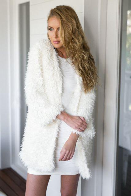 Modelo usa vestido e casaco de pelo na cor branca.