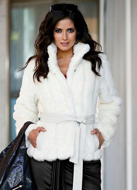 Modelo usa calça preta, casaco de pelos branco e bolsa de mao preta.