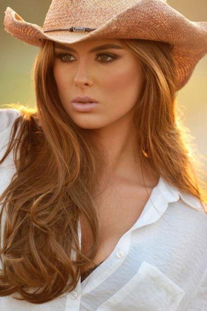 Modelo usa chapéu de palha country caramelo e camisa branca.