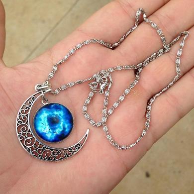 Colar de metal com desennho de lua e pedra azul grande redonda.
