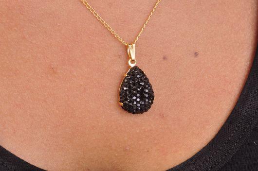 Colar de mini pedras pretas cravejadas e corrente de ouro banhado.