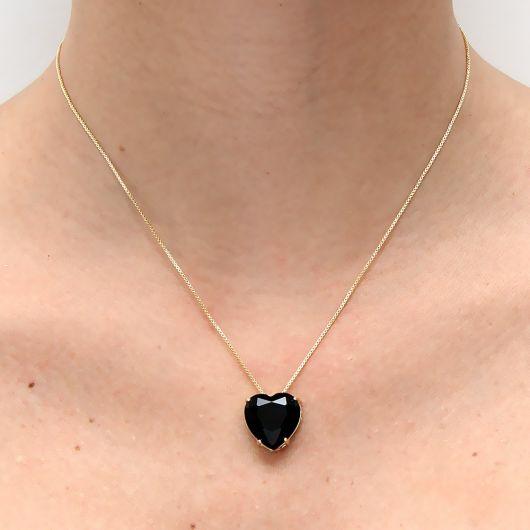 Colar de pedra preta com formato de coração e corrente fina em ouro.