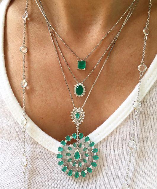 Mulher veste três colares com corrente de prata e pedras na cor verde esmeralda.