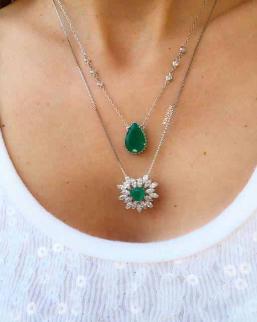 Mulher veste dois colares de pedra verde um em formato de lágrima o outro em formato de flor.