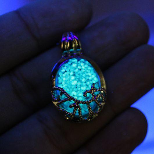 Colar de pedra azul redonda que brilha no escuro com detalhes de metal tramado ao seu redor.