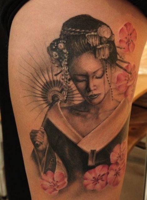 Tatuagem de gueixa do busto para cima, com quimono em tons de preto e branco com fundo de flores cor de rosa.