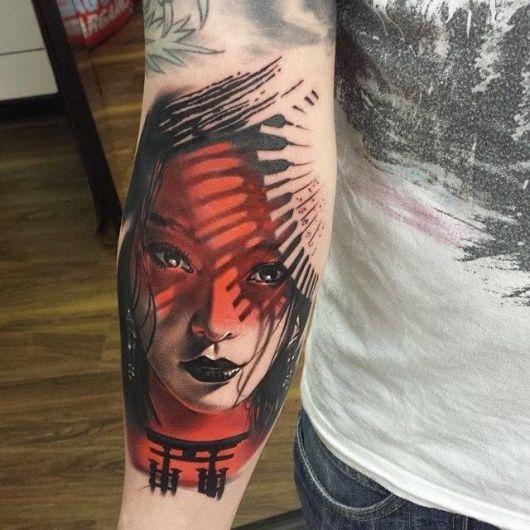 Rosto de gueixa tatuado nas cores vermelho e preto com traço delicado.