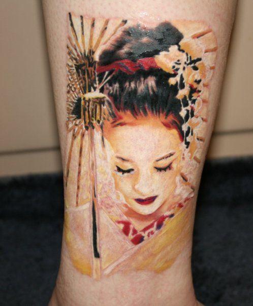 Tatuagem de gueixa com guarda chuva, colorida nas cores vermelho, amarelo, preto e branco.