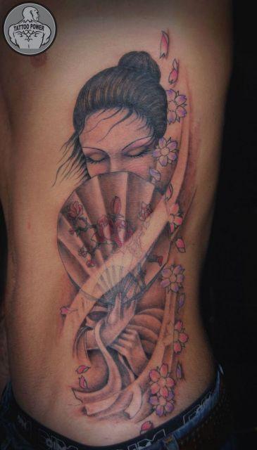 Tatuagem de gueixa com meio rosto coberto por leque, traço fino colorida com tons de rosa claro.