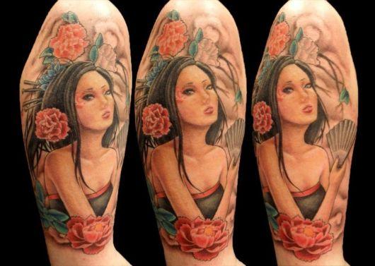 Gueixa tatuada no braço com flor de lotus colorida.