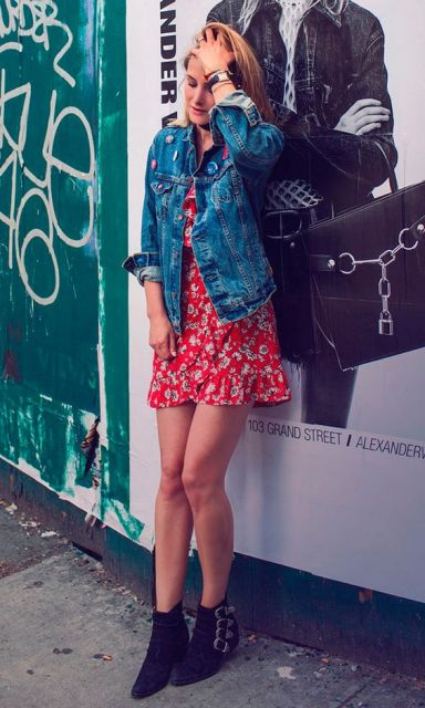 Mulher com vestido vermelho estampado e jaqueta jeans.