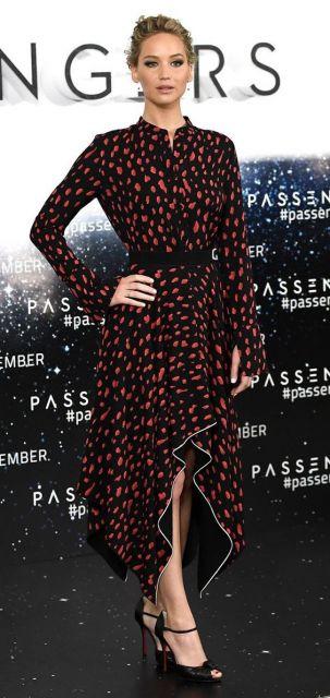 Jennifer Lawrence com vestido preto com estampa vermelha.
