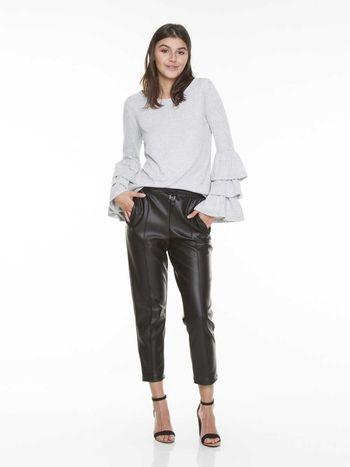 Modelo usa calça marrom de couro, blusa de três babados na manga e sandalia preta.