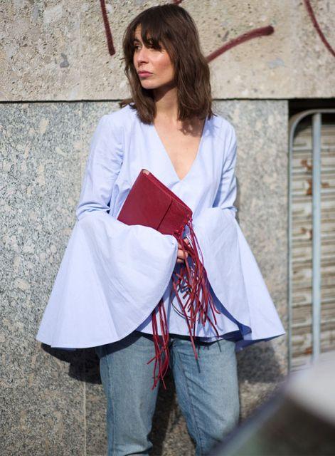 Modelo usa calça jeans, blusa manga longa com detalhe de babado na manga e bolsa na cor bordô.