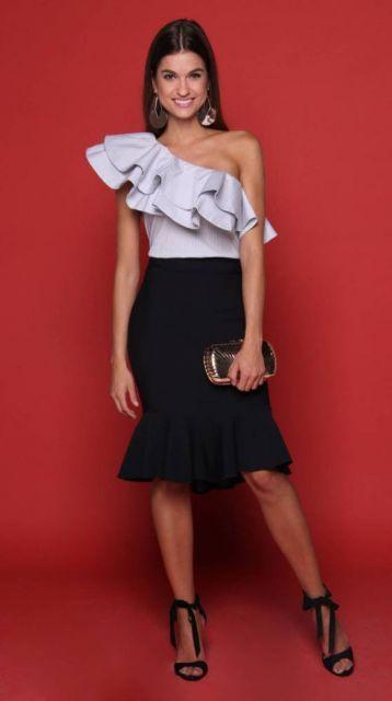 Modelo usa sia preta, blusa decote de babados azul clara e sandalia preta, com clutch dourada.