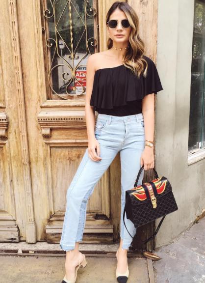 04a4ff746 Modelo usa calça jeans clara, blusa preta com decote de babado de um ombro  só