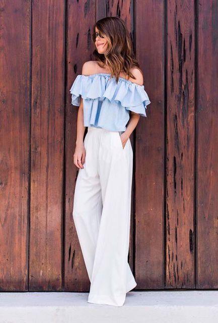 Modelo usa calça pantalona branca, blusa de babdo azul.