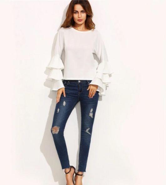 Modelo usa blusa de babados manga longa, calça jeans destruída e sandalia preta.