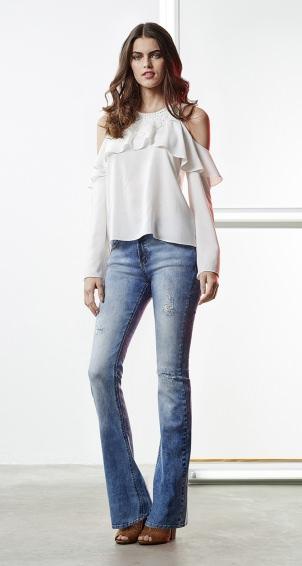 Modelo usa blusa branca de babdos,calça flare jeans e sapato de salto.