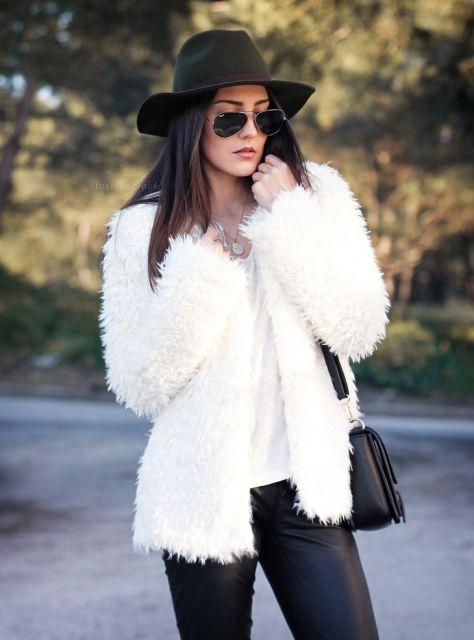 Modelo veste casaco de pelo branco, blusa branca, calça preta e bolsa preta com chapéu na mesma cor.