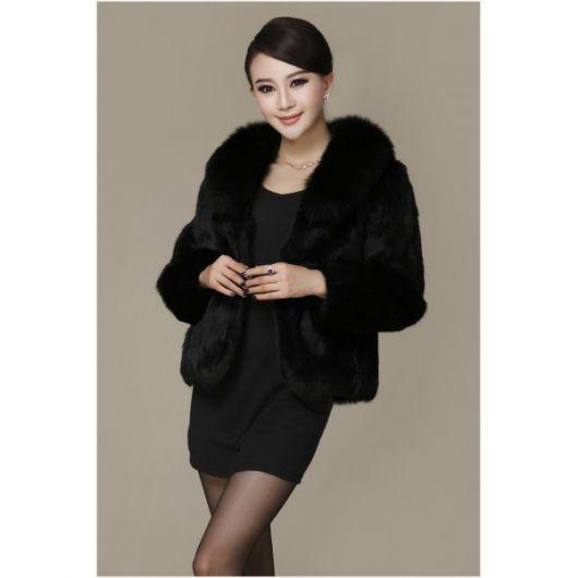 Modelo usa vestido preto, meia calça e casaco de pelos preto.