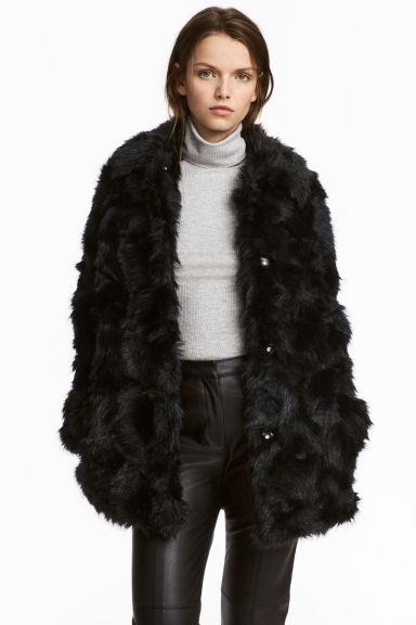 Modelo usa casaco de pelinhos preto, blusa cinza com gola alta e calça preta de couro.