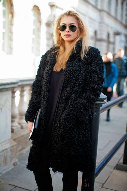Modelo usa casaco de pelinhos preto longo, calça preta e blusa na mesma cor.
