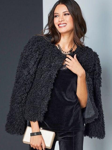Modelo usa casaco preto de pelinhos, macacão preto de veludo e clutch dourada.