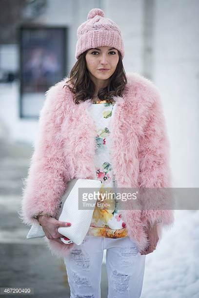 Modelo usa touca rosa, casaco rosa de pelos, blusa colorida e calça branca.