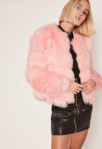 Modelo usa saia preta de couro, blusa preta e casaco de pelinhos cor de rosa.