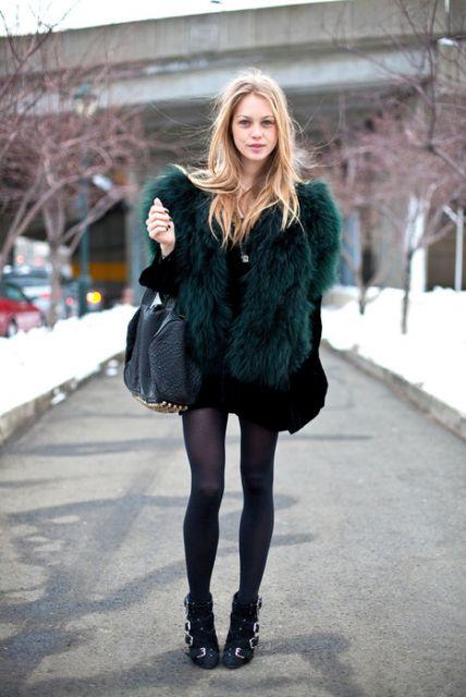Modelo usa bota preta, meia, vestido e casaco de pelo verde escuro com bolsa preta.