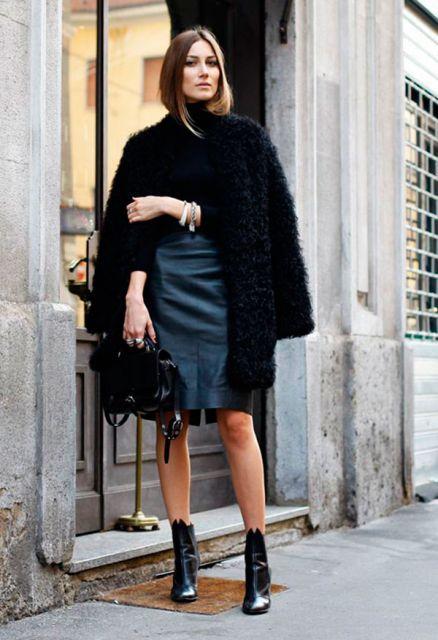 Modelo usa saia azul, bota, casaco de pelo preto longo e bolsa na mesma cor.